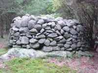 Vertically walled cairn on bedrock